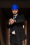 Het knappe Horloge van Looking At His van de Bouwmanager royalty-vrije stock foto