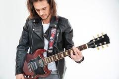 Het knappe jasje die van het jonge mensen zwarte leer elektrische gitaar spelen Stock Foto's