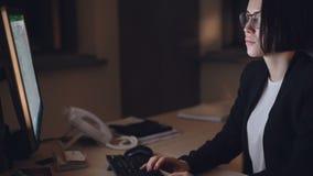 Het knappe jonge brunette werkt aan computer in bureau bij nacht concentreerde zich op onvolledig zeker project en stock footage