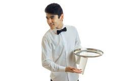 Het knappe jonge kelners` s overhemd die kijkt aan de kant en het houden van een dienblad glimlachen stock fotografie