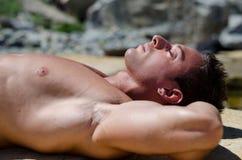 Het knappe jonge mens leggen naakt op witte rotsen, gesloten ogen Stock Fotografie