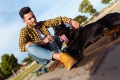 Het knappe jonge mens spelen met zijn hond in het park Royalty-vrije Stock Afbeeldingen