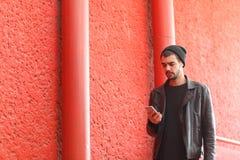 Het knappe jonge mens stellen op de camera op een rode achtergrond Stock Foto's