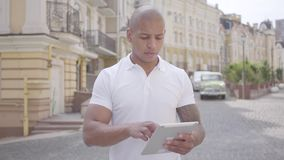 Het knappe kale zakenman typen van het Middenoosten op de tablet die op de stadsstraat tanding Freelance concept Het werken van d stock footage