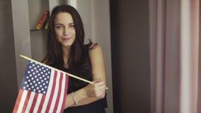 Het knappe meisje bevindt en houdt zich binnen een Amerikaanse vlag stock videobeelden