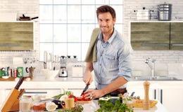 Het knappe mens koken in keuken thuis Stock Afbeeldingen