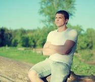 Het knappe mens ontspannen op een aard, zachte zonnige zonsondergang Royalty-vrije Stock Fotografie
