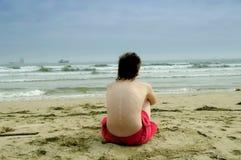 Het knappe mens ontspannen op het strand stock foto's