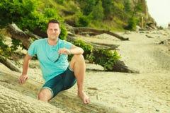 Het knappe mens ontspannen op strand tijdens de zomer Royalty-vrije Stock Foto's