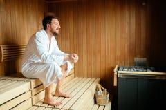 Het knappe mens ontspannen in sauna stock foto's