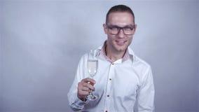 Het knappe mens vieren met glas champagne over grijze achtergrond stock footage