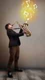 Het knappe musicus spelen op saxofoon met muzieknoten Royalty-vrije Stock Afbeeldingen