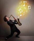 Het knappe musicus spelen op saxofoon met muzieknoten Royalty-vrije Stock Foto