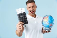 Het knappe opgewekte gelukkige volwassen mens stellen geïsoleerd over blauw muur achtergrondholdingspaspoort met kaartjes en bol royalty-vrije stock fotografie