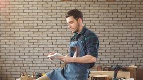 Het knappe schrijnwerkerswerk in timmerwerk Hij is succesvolle ondernemer op het zijn werk stock video
