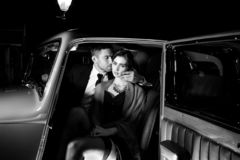 Het knappe sexy paar, knappe man in kostuum, mooie vrouw in rode kleding, omhelst passionately in uitstekende auto royalty-vrije stock foto
