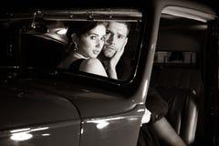 Het knappe sexy paar, knappe man in kostuum, mooie vrouw in rode kleding, wordt ontdekt omhelzend in uitstekende auto stock foto's