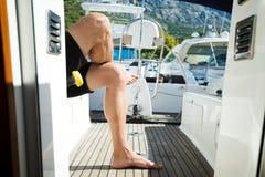 Het knappe sterke mens ontspannen op zijn boot Royalty-vrije Stock Afbeelding