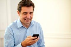 Het knappe zakenman texting met zijn cellphone stock afbeeldingen