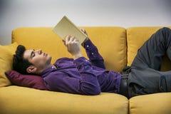 Het knappe zwarte haired boek van de jonge mensenlezing bij Stock Fotografie