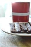 Het knapperige donkere brood van de chocoladestok eet paar met koffie in rode kop Stock Foto