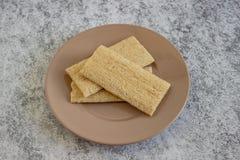Het knapperige geheel van het roggebrood in plaat op oude lijst stock afbeelding