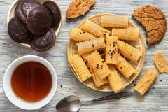 Het knapperige wafeltje rolt in een plaat met thee en chocoladeschilferkoekjes, hoogste mening stock fotografie