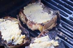 het knoflook encrusted lapjes vlees die terwijl zij op de grill sissen roken stock footage