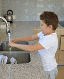Het knoflook van de kindwas in de keuken stock foto's