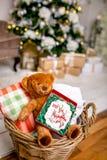 Het koekje met deers en nummer 2019 in kartondoos op een teddybeer in een rieten mand voor defocused lichten van Kerstmisdeco stock fotografie