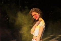 Het koele donkerbruine vrouw stellen in een wolk van gele droge verf Holi a Stock Foto
