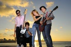 Het koele jonge muzikale band stellen bij zonsondergang Stock Fotografie