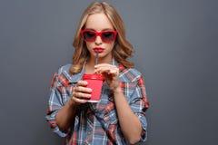Het koele meisje draagt donkere glazen met rode rand Zij drinkt cokes van de rode kop Geïsoleerd op grijze achtergrond Royalty-vrije Stock Afbeeldingen