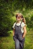 Het koele meisje is een hipster in donkere glazen en overall Stock Afbeelding
