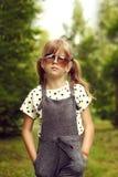 Het koele meisje is een hipster in donkere glazen en overall Stock Foto
