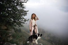 Het koele Meisje en hondverblijf van border collie op rand van rots in mist kijkt vooruit in canion kijkt in camera stock afbeeldingen