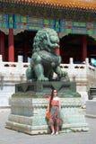 Het koele modieuze vrouwelijke westelijke toerist stellen met Chinees draakstandbeeld stock fotografie