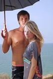 Het koesteren van jong paar op een strand Stock Foto's