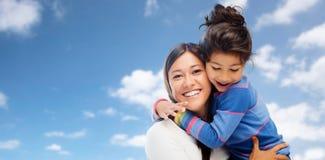 Het koesteren van moeder en dochter over hemelachtergrond Royalty-vrije Stock Afbeeldingen