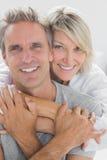 Het koesteren van paar die bij camera glimlachen Royalty-vrije Stock Afbeelding