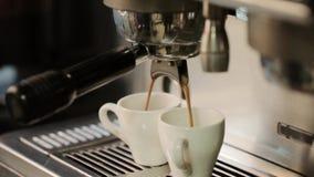 Het koffiezetapparaat giet hete koffie in twee witte koppen De handen nemen het stock videobeelden