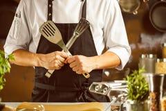 Het koken, beroep en mensenconcept - mannelijke chef-kokkok die voedsel maken bij restaurantkeuken royalty-vrije stock foto's