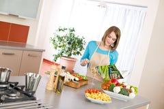 Het koken - de lezingskookboek van de Vrouw in keuken stock foto