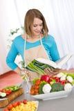 Het koken - de lezingskookboek van de Vrouw in keuken royalty-vrije stock foto