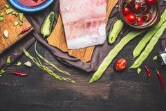 Het koken en de voorbereiding van visfiletsschotels met slabonen, tomaten en ingrediënten op donkere houten achtergrond stock afbeeldingen
