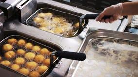 Het koken in hete kokende olie in de frituurpan De kok bereidt voedsel voor Smakelijk vettig voedsel Snel voedsel stock video