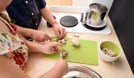 Het koken met kinderen Jonge geitjes met messen in stuk speelgoed keuken stock foto