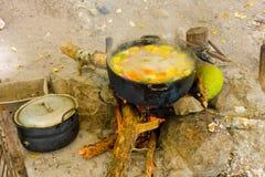 Het koken op een open brand in de keerkringen stock foto