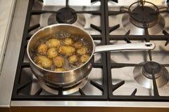 Het koken potatos op het fornuis Stock Foto