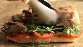 Het koken procédé die de sandwich van het braadstukrundvlees met arugula van de tomatenkomkommer maken stock footage